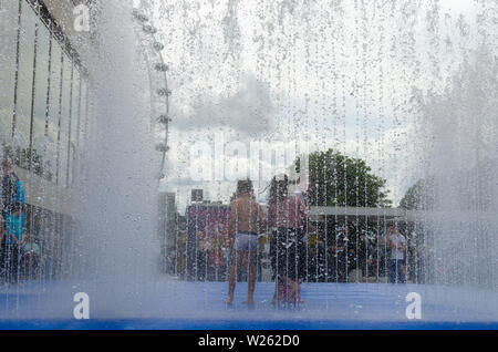 Children cooling down in the summer heat wave inside a fountain in London, England - Stock Photo