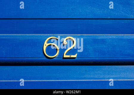 House number 62 with the sixty-two in metal digits on a bright blue wooden front door - Stock Photo