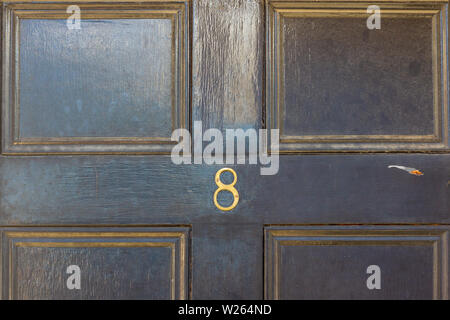 House number eight with the 8 in metal digits on a wooden front door - Stock Photo