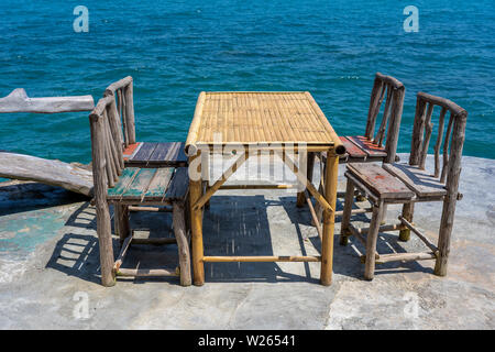 Bamboo table and wooden chairs in empty cafe next to sea water in tropical beach. Close up. Island Koh Phangan, Thailand - Stock Photo