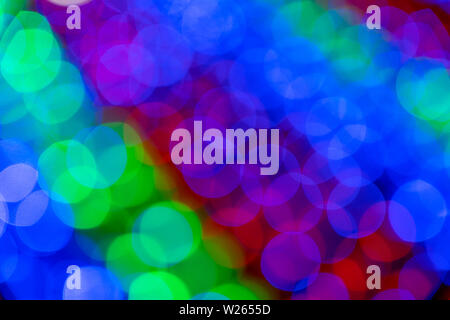 Blurry multicolored garland with glowing lights. Christmas, new year, birthday and wedding concept . Blurred background, bright colored light bulbs, l - Stock Photo