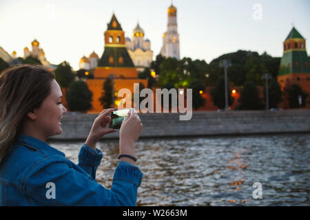 Woman tourist taking pictures on mobile phone during the boat trip on the Moscow river on the background the Kremlin. Travel to Russia concept. - Stock Photo