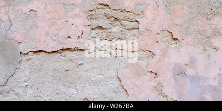 Old weathered painted wall background texture. Light grey pink dirty peeled plaster wall with falling off flakes of paint - Stock Photo