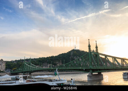 Budapest, Hungary - 15 June 2019: Cruise ships on Danube river and Gellert Hill at sunset - Stock Photo