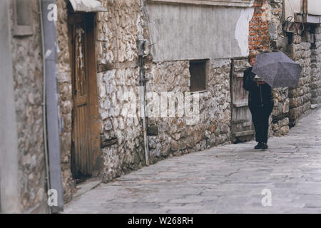 Ohrid, Northern Macedonia -  April 2019 : Woman with umbrella walking on a narrow street in Ohrid town - Stock Photo