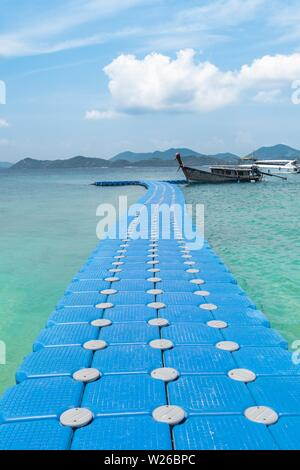 A shot of blue plastic dock floating over the sea with a wooden ship parked next to it - Stock Photo