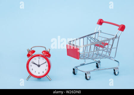 Christmas gifts and alarm clock in a supermarket trolley on a blue background with free space for text - Stock Photo