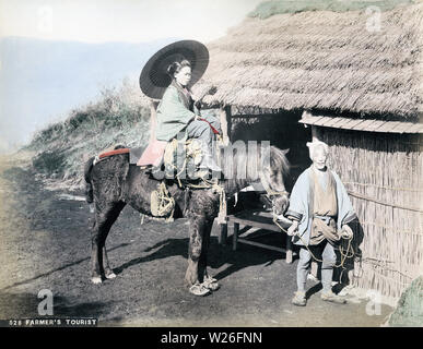 [ 1890s Japan - Japanese Woman on Horse ] —   A female traveller holding a parasol rides a pretty sad looking horse held by a farmer. The thatched building appears to be a resting place.  19th century vintage albumen photograph. - Stock Photo