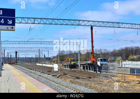 Crane and excavator work on the construction site on the railway, laying rail, building a railway station - Stock Photo