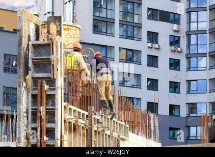 Workers poured concrete in the formwork of the walls on the construction of the new house against the background of a modern residential building. - Stock Photo