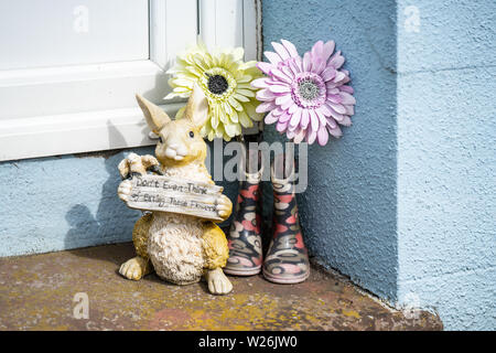 Castletown,Isle of Man, June 16, 2019.Bunny Rabbit Home or Garden Animal Figurine, Statue, flowers and a pair of wellingtons.Funny message in english. - Stock Photo