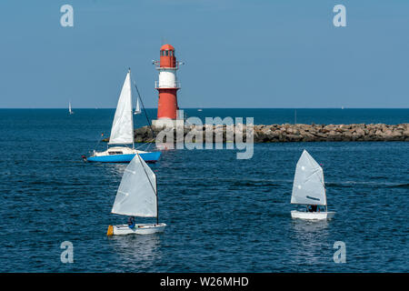 east pier with red beacon and little white sailingboats in Warnemuende - Stock Photo