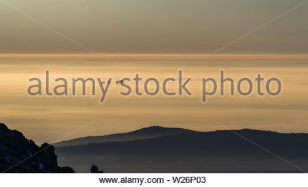 View of the sunrise with the skyscrapers of Madrid in the middle of the foggy landscape from the mountains - Stock Photo