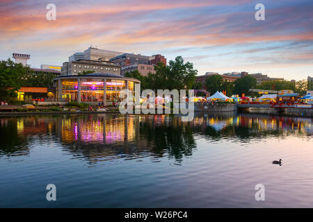 Looff Carousel is colorfully illuminated and reflects in the river alongside festival tents and shops during Pig Out in the Park, Spokane Washington - Stock Photo