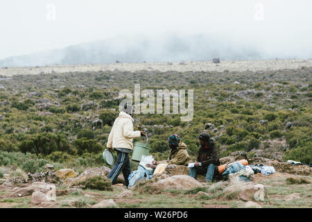 Porters having lunch in Shira 1 Camp on the way to the top of Mount Kilimanjaro in Tanzania - Stock Photo