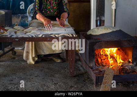 Old arab woman cooking traditional bedouin cuisine food - taboon bread or flatbread. Close up of Arab woman hands baking fresh dough for Taboon bread or Laffa. Middle Eastern and Israel flat bread. - Stock Photo