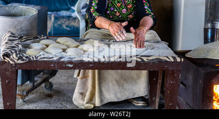 Close up of old Arab woman hands kneading fresh dough for Taboon bread or Lafah is a Middle Eastern flatbread also called lafa or Iraqi pita. - Stock Photo