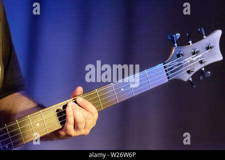 Guitarist plays on of bass guitar, close up .  - Stock Photo