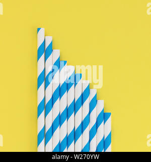 Set of blue striped paper straws on a yellow background