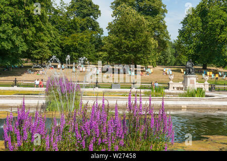 LONDON ENGLAND - JULY 15 2013;  Ornamental Italian Gardens in Kensington Gardens with bronze statue of Jenner and people sunbathing in deck-chairs on - Stock Photo