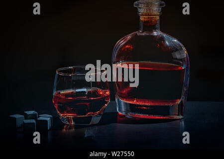 Glass of brandy served cold with decanter and chilling blocks on a dark shadowy bar counter at night - Stock Photo