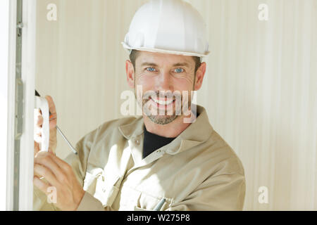 happy man installing bay window in a new house - Stock Photo
