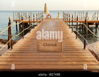 A wooden plate with the inscription closed hanging on the aisle to the pier - Stock Photo