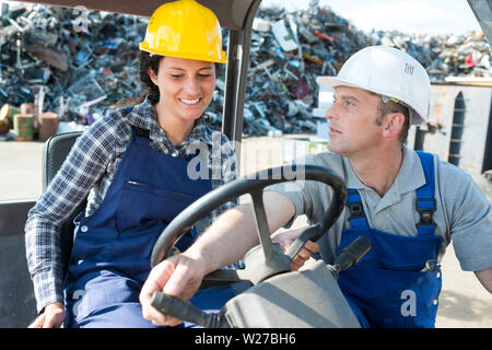 manager and woman forklift truck driver in an industrial area - Stock Photo