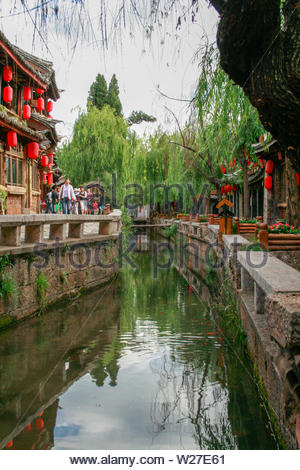 China, LiJiang - May 30, 2008- Street on a Chinese waterway. 800-year-old area of the city with cobblestone streets, streams, bridges & traditional Na - Stock Photo