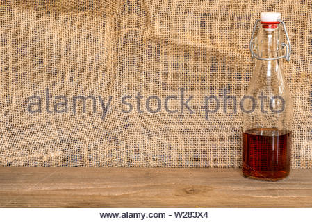 dark amber liquid in a bottle against a burlap backdrop - Stock Photo
