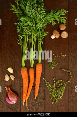 Fresh from the farm raw carrots with tops with crimini mushrooms, garlic cloves, shallots, oregano and thyme sprigs on dark rustic wooden background f