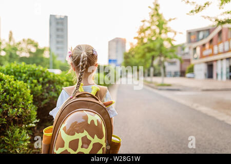 Kid girl pupil from behind walking back to home after learning study school alone with schoolbag, preschool and kindergarten education concept. First - Stock Photo