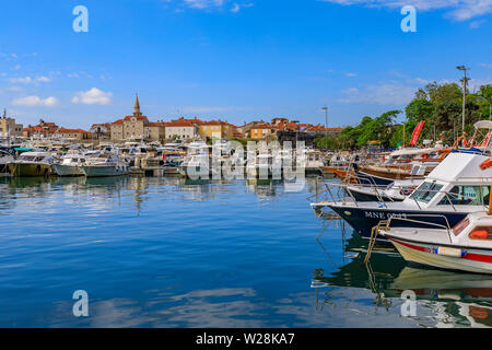 Budva, Montenegro - May 30, 2019: Anchored boats in the port and marina by the medieval Old town on the Adriatic Sea - Stock Photo