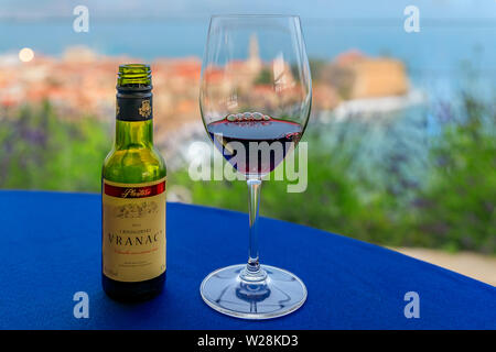 Budva, Montenegro - May 27, 2019: Glass and small bottle of local red wine Vranac at a restaurant with Old Town and Adriatic Sea blurred in background - Stock Photo