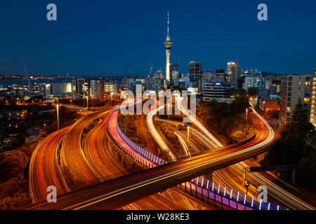 Motorways, Lightpath cycleway, and Sky Tower at dusk, Auckland, North Island, New Zealand - Stock Photo