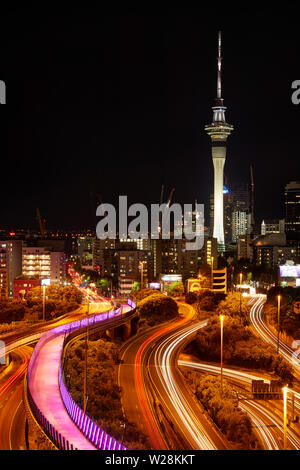 Motorways, Lightpath cycleway, and Sky Tower at night, Auckland, North Island, New Zealand - Stock Photo