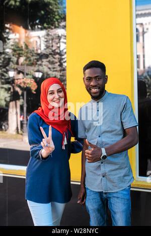 Black man and Muslim women, best friends posing at camera at the street. - Stock Photo