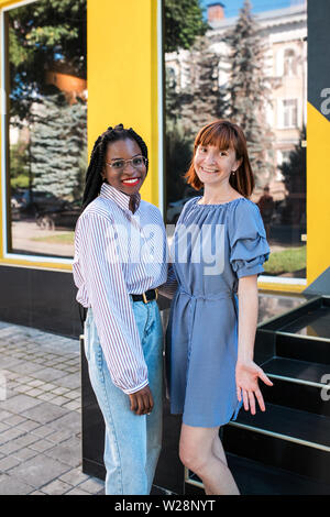 Caucasian and Muslim women, best friends posing at camera at the street. - Stock Photo