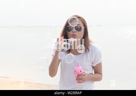 Cute girl blowing bubble on the beach - Stock Photo
