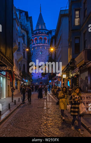 Night view of a street near Galata Tower, a medieval stone tower in Istanbul and popular tourist attraction. Istanbul, Turkey, October 2018 - Stock Photo