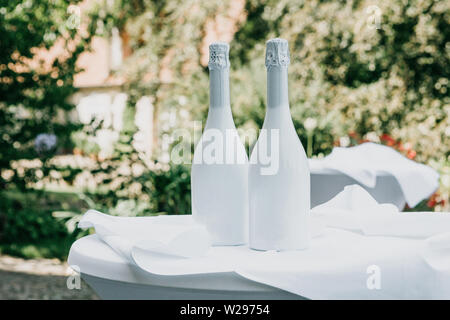 Two white champagne bottles on the table. Festive concept. - Stock Photo