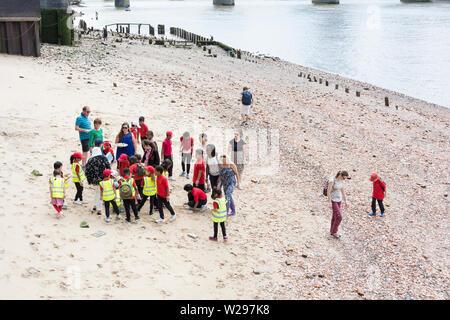 Mudlarking school trip to Thames foreshore, City of London, UK - Stock Photo
