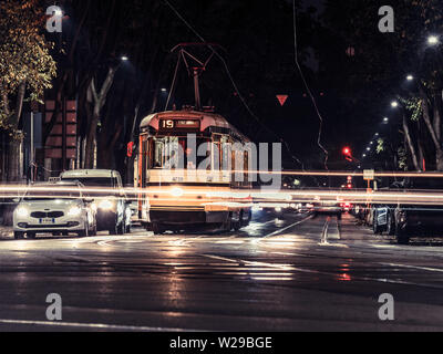 Milan, Italy, 09/11-18. A yellow tram has stopped, waiting for green light in a busy intersection. - Stock Photo