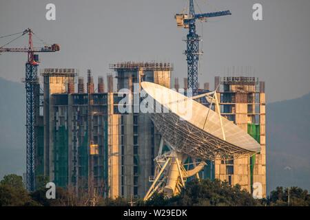 Large satellite dish on the building onstruction background - Stock Photo