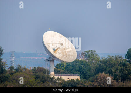 The Large satellite dish on the forest over clouded background - Stock Photo