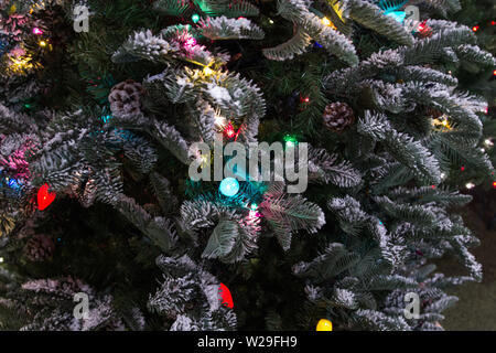 Festive Holiday Background. Christmas tree decorated with ornaments and illuminated with multi colored lights in panoramic orientation - Stock Photo