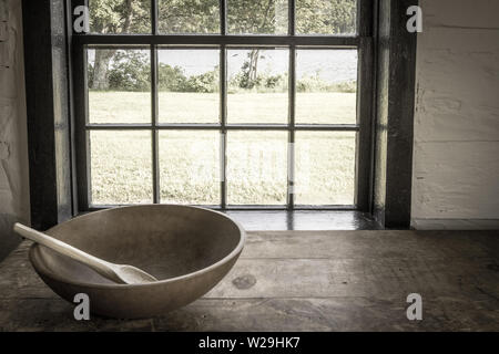 Country Kitchen Interior. Rustic style kitchen with wooden spoon and bowl on antique wooden table - Stock Photo