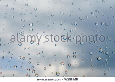 Cloudy days, raindrops on the Windows. Rainy weather, rain background and bokeh. Drops of water on the window glass against the blue sky after a showe - Stock Photo