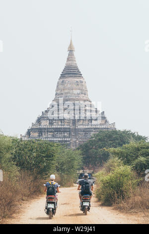 Young couple riding electric scooters towards Shwesandaw pagoda of ancient Bagan temple complex in Myanmar - Stock Photo