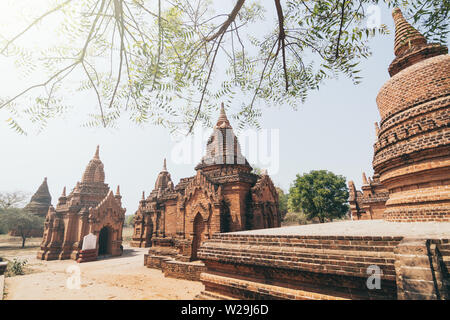 View over stupas and pagodas of ancient Bagan temple complex during sunrise golden hour in Myanmar. - Stock Photo